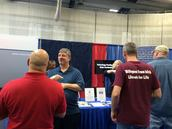 MNCDHH's exhibit table at Deaf Nation with people surrounding it