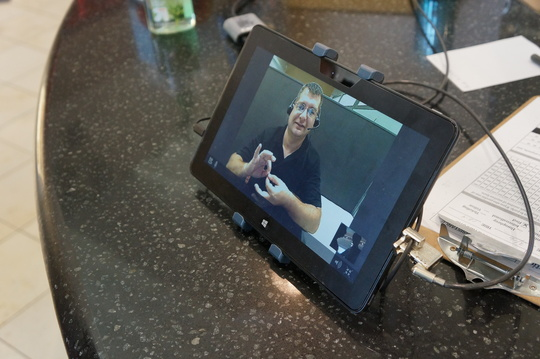 A VRI interpreter is visible within a tablet. He is signing 'interpreter.'