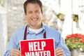 Man holding help wanted sign