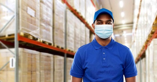 A Black worker wears a protective face mask while at work