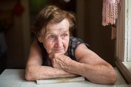 Elderly woman alone looking out window
