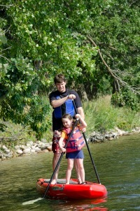 father and daughter paddleboarding