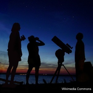 silhouette of three people and telescope