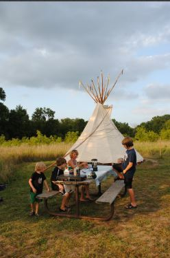 family picnicking near tipi