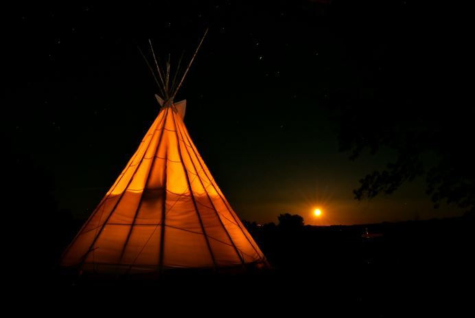 tipi at night under moon