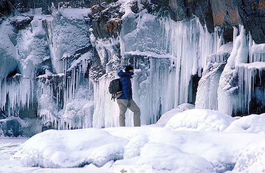 hiker near frozen falls at Cascade River State Park