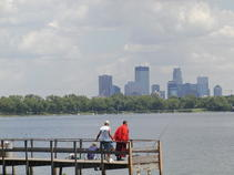 Several anglers on fishing dock on Lake Calhoun with Minnepolis skyline in background