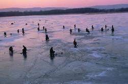 People icefishing on lake at sunset