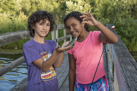 Two kids showing off their catch