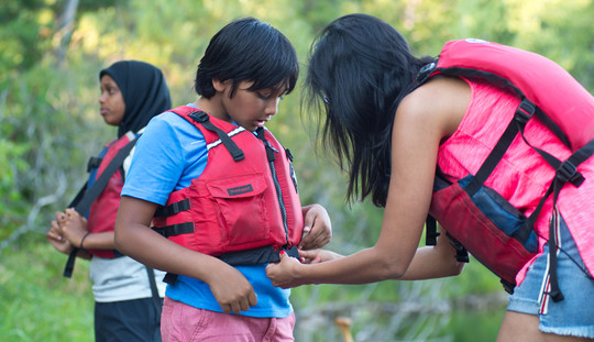 Mom helping son with life jacket