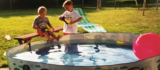 Temporary pool with 2 boys filling water toys