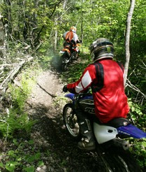 two off highway motorcycle riders on trail