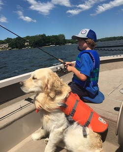 A boy fishing in a boat with his dog. Both are wearing life jackets.