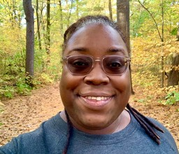 Woman smiling with trail and fall trees in background