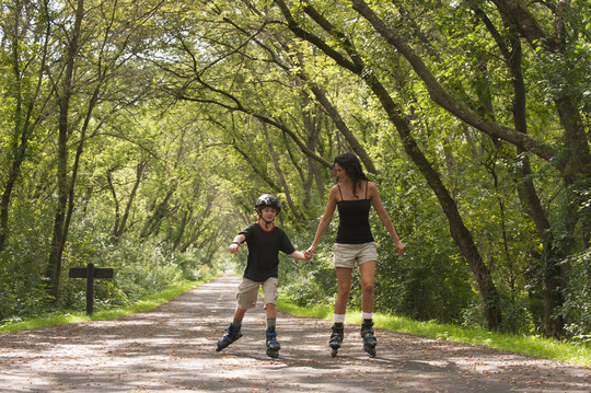 Mom and son rollerblading on a paved trail
