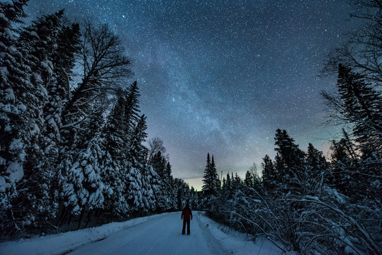 man in winter observing milky way at Grand Portage