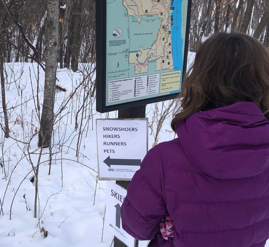 Child reading map and direction signs