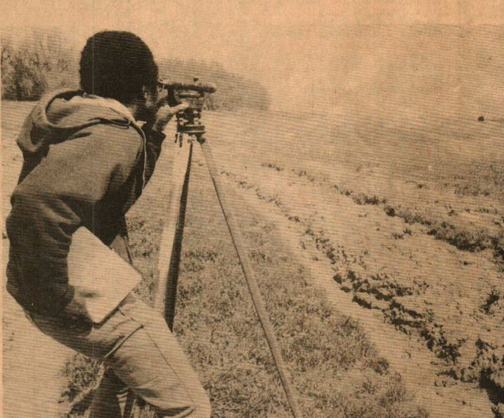 Sepia image of man surveying land