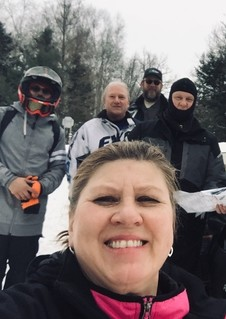 Woman smiling with a group of men in the background in snowmobiling outfits