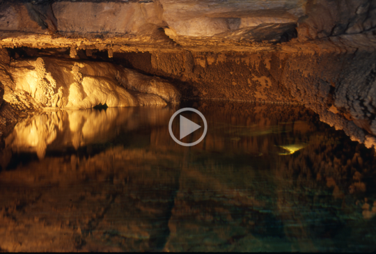 Inside of a lake inside a cave with video play button