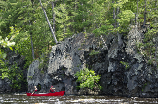 Red canoe with two paddlers with cliffs in background