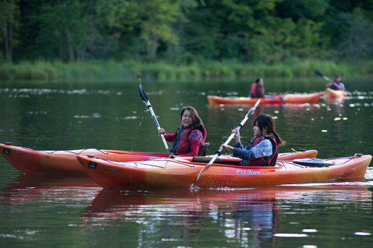 Mom and daughter in separate red kayaks