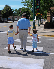Man and two children cross street