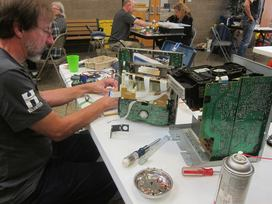 People working with electronics at March fix-it clinic