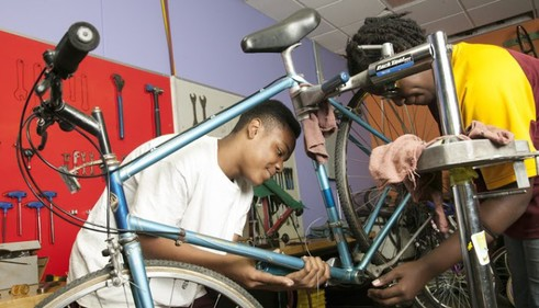 Youth repairs bike
