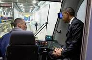 Metro Transit employee Rick Carey shows President Obama the controls of a new light rail vehicle