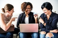 Photo of three women sitting around a laptop and laughing