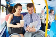 Photo of woman and man sitting by each other on a bus, holding a paper coffee cup and work papers
