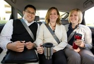 Photo of a man and two women wearing business clothes and holding to-go coffee mugs sitting together in a van or car