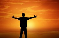 Photo of a man standing with arms outstretched in front of a sunset