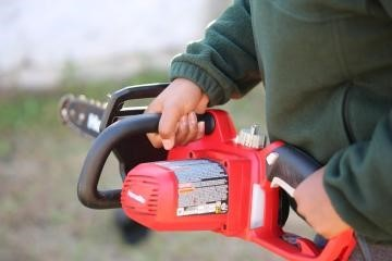 person holding an electric chainsaw