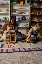 Two kids and mom playing with toys at the Minneapolis Toy Library
