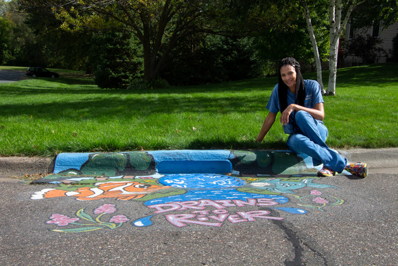 Kim Carpenter sitting by storm drain mural