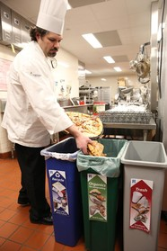Chef putting food into organics recycling container