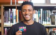 Young person holding a library card