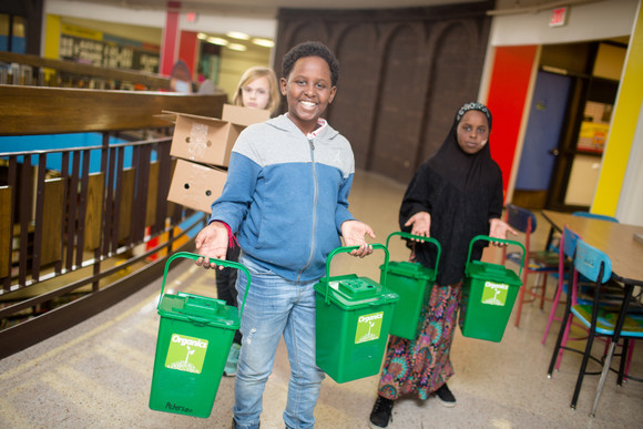 Students taking out organics recycling from their classroom