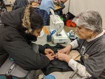 Fix-It Clinic volunteer helping woman make a sewing repair