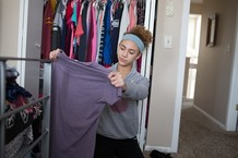 Teenage girl looking at shirt and cleaning out closet