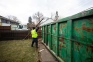 Building materials being thrown into recycling dumpster
