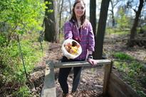 Woman putting food scraps into backyard compost bin
