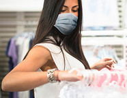 Woman wearing a mask browsing clothing racks