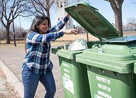 Woman putting bag of organics into drop-off organics recycling cart