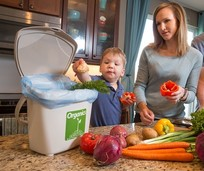 Boy putting food in organics container while mom watches
