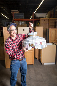Man at building material reuse store holding up antique lamp