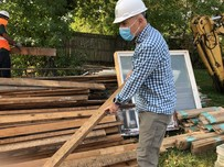 Man carrying piece of lumber being salvaged in deconstruction project