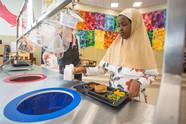 Girl putting milk carton into recycling bin in school cafeteria
